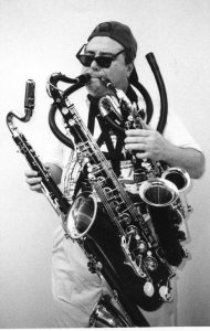A guy playing multiple saxophones